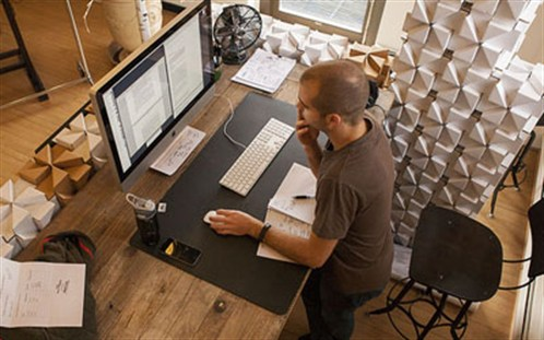 Man At Standing Desk In Office